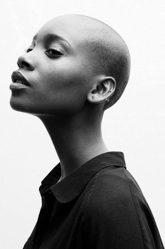 photo femme noir et blanc, dame au crâne rasé et aux traits très beaux, nez et bouche charnus, femme vêtue avec chemise noire