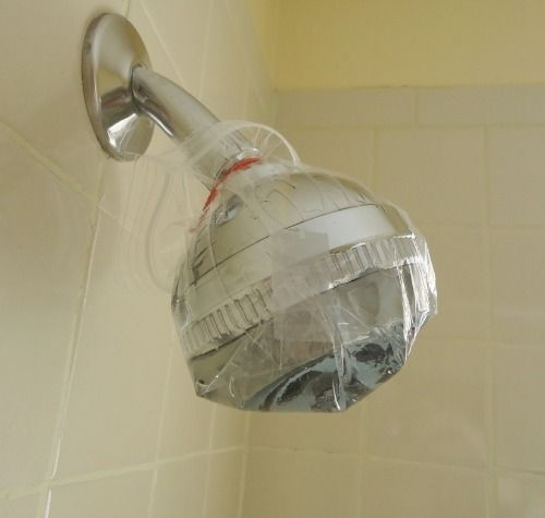 How to Clean a Shower head with Vinegar: 1.  Fill a baggie about a quarter to half full with vinegar. Do not dilute vinegar with water.    2. Secure it in place with a rubberband. Make sure the vinegar stays in contact with the shower head. I used a little bit of tape too, to get the baggie in the position I wanted.    3. Set for 4hrs