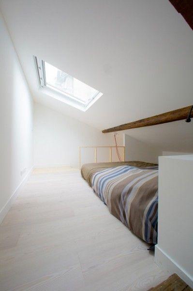 リノベーションでロフトを追加したワンルームマンションのロフトの勾配天井の下の天窓付きベッドルーム1