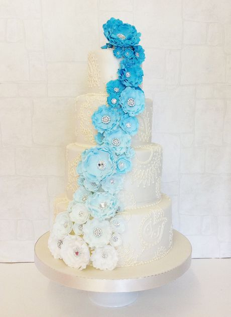 "A stunning ivory cake featuring intricate mehndi style piping with a pearlised lustre finish.   The delicate hand made sugar flowers cascade down the cake fading from a rich turquoise to white and finished with sparkling non edible diamanté centres.   As seen: 4"", 6"", 8"" and 10"" all 1.5 normal depth."