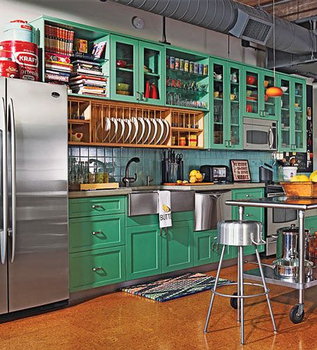 A gorgeous loft kitchen with green cabinets and cork floors