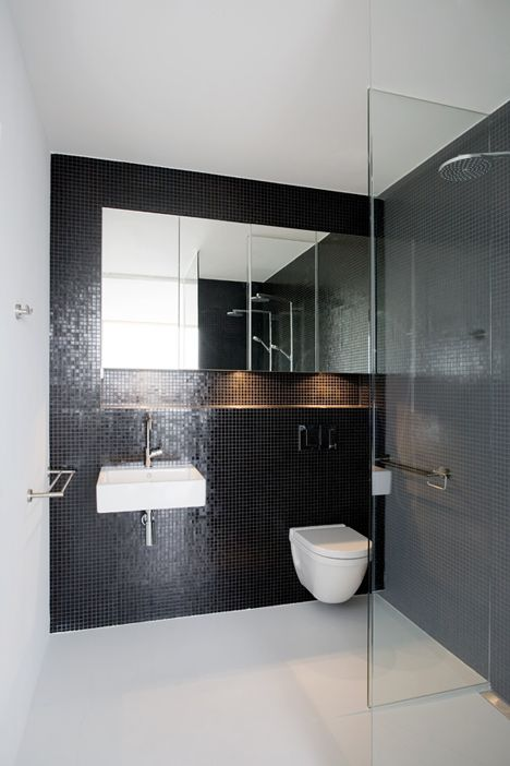 #reforma #baño con lavabo sin pedestal en pared de gresite color negro, zona de ducha con separación de vidrio, suelo microcemento.
