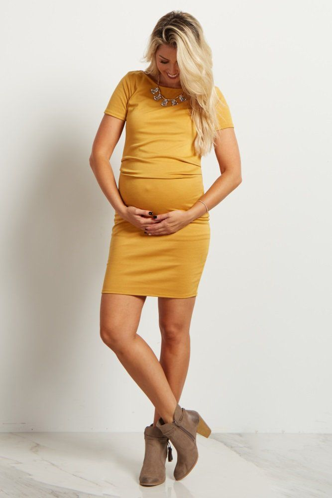 A form-fitting solid hued maternity dress featuring a rounded neckline, short sleeves, and ruched sides.