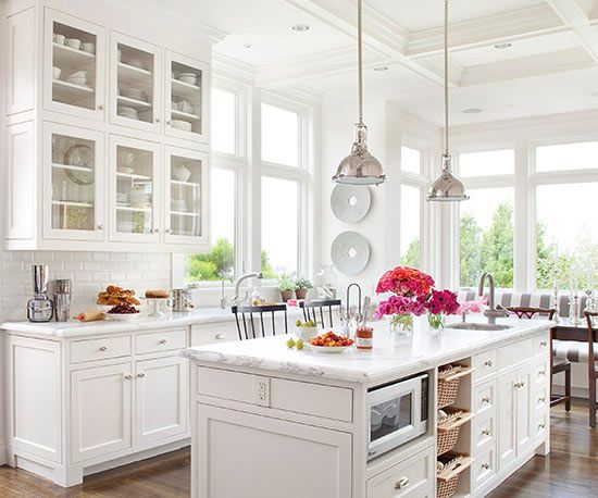 White beveled subway tile blends into the all-white cabinetry and countertops in this kitchen.