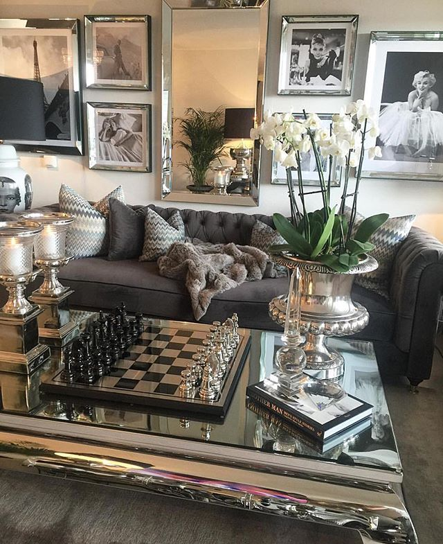 black and white photos in mirror frame reflective table top the soft to touch fabric live plant contributed to this elegant living room