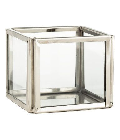 Gold-colored. Small tea light holder in clear glass with a metal frame and base. Size 2 x 2 1/4 x 2 1/4 in.