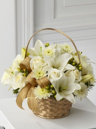 A Christmas arrangement of all white flowers and decorations in a gold basket