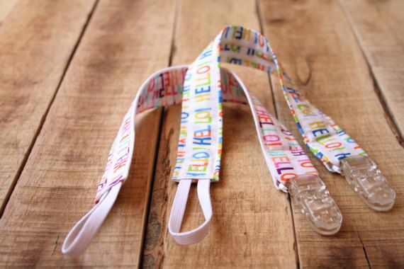 Keep your childs soother close by with this cute HELLO print universal soother clip/pacifier clip. Made with 100% cotton in one of two colourful Hello patterns.  It comes with an elastic on one end that loops through any soother clip or toy. On the other end it has a sturdy clip that attaches easily to clothing that cannot be removed by child. This universal soother clip is 1 wide and is 13 long. It is top stitched for durability  Makes a great toy strap as well! Easily attaches to toys ...