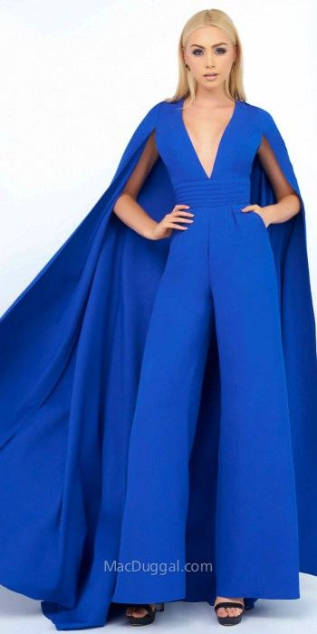 Be one in a million in the unforgettable V-Shape Wide Leg Jumpsuit with Floor Length Cape by Mac Duggal. This striking ensemble features a V-shape neckline, a sleeveless bodice and a closed back. This wide leg jumpsuit also includes classic princess seams, a pleated waistband, side pockets and a floor length cape. #edressme