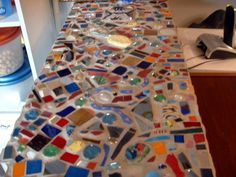 "Mosaic countertop. - GLASS CRAFTS. ""Recycled glass, tumbled glass tiles, tumbled pottery shards, broken beads and some fused pieces. Grouted with sanded grout and sealed.   Read more: http://www.craftster.org/forum/index.php?topic=321803.0#ixzz2aitCHW30"""