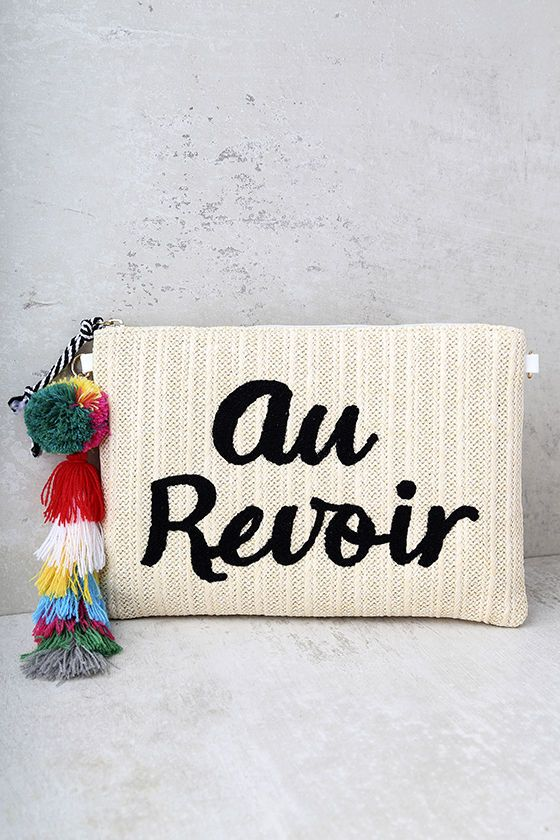 """Wave goodbye to the real world from your cozy cabana, with the Melie Bianco St. Tropez Au Revoir Beige Woven Clutch by your side! This woven clutch has """"Au Revoir"""" embroidered in black, a multi color pompom/tassel pull, and three interior pockets. Carry as a clutch by the detachable wristlet, or attach the 44"""" gold chain strap."""