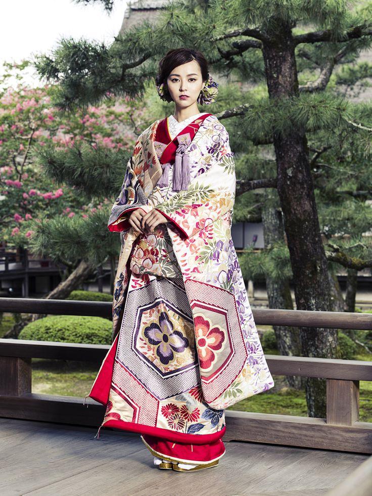 色打掛(Iro Uchikake)/大きな亀甲で場面を斜めに仕切り、左上部には花房が豊かな藤の花、右下部には清雅な菊の花を配した正徳期の小袖らしい構図の総絵羽錦織の打掛です。花嫁衣装らしく華やぎを持たせるために交互に赤地の鹿の子文様を配しました。気品と大胆さを併せ持った衣裳です。
