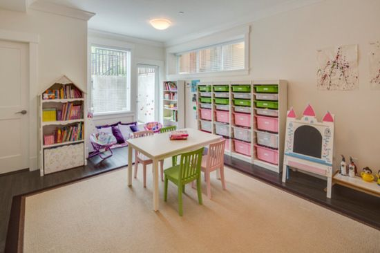 This Children's play area is bright, functional, and efficient with storage cubbies in bright colours, and a wide open area for toys and playing!