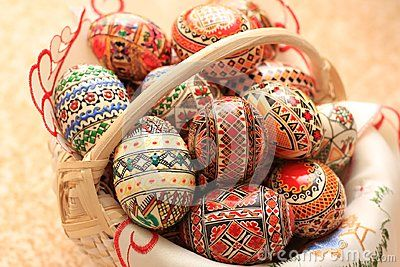 Decorated eggs in a basket. Traditional Easter eggs painted with multiple colors. Red, green, blue, brown and black lines, shapes, traditional paintings. The Easter eggs are sitting on a romanian traditional embroidery towel. The basket is made of cream color twigs.