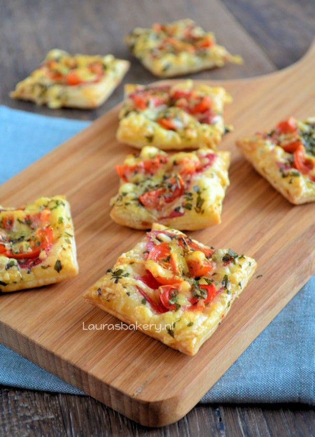 Supersnelle mini-pizza. Kleine vierkantjes bladerdeeg bestrijken met tomaat, besprenkelen met kaas en kruiden. In de oven en klaar..
