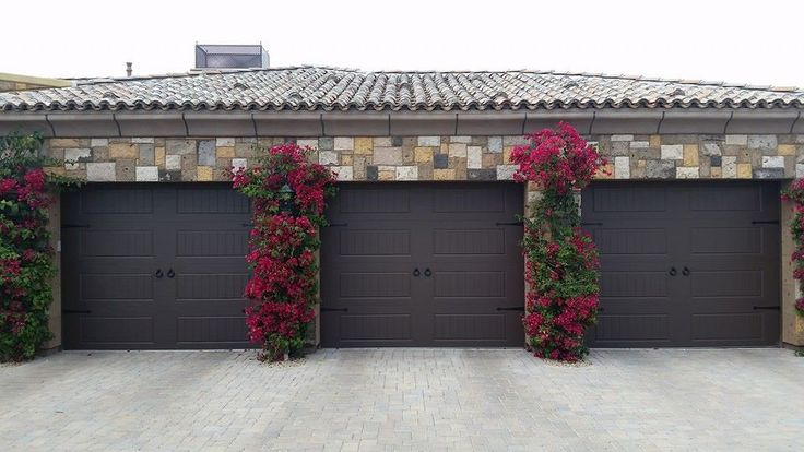Move over plain vanilla garage doors - choose chocolate brown instead to warm up your home's exterior and complement other exterior details like this stone surround. Model shown: Clopay Gallery Collection steel carriage house door installed by Stapley Action Garage Door. www.clopaydoor.com