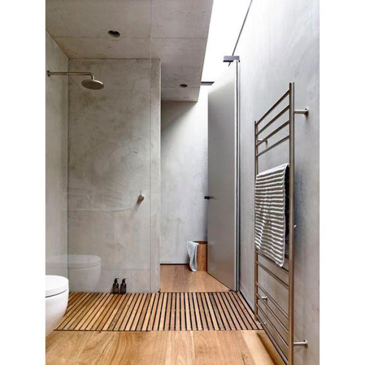 Enquanto o piso imita madeira, as paredes e tetos foram revestidas com cimento queimado - o suporte para toalhas finaliza a decór