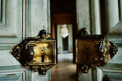 door opening with a glimpse of distant chandelier