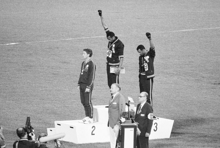 Tommie Smith and John Carlos, gold and bronze medalists in the 200-meter run at the 1968 Olympic Games, engage in a victory stand protest against unfair treatment of blacks in the United States. With heads lowered and black-gloved fists raised in the black power salute, they refused to recognize the American flag and national anthem. Australian Peter Norman is the silver medalist.