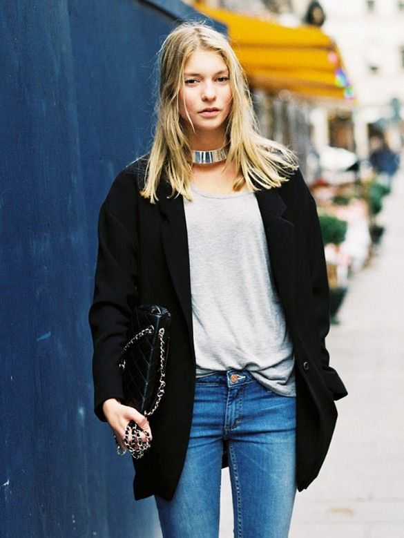 A gray t-shirt is tucked into skinny jeans and paired with a black jacket, black purse, and silver choker