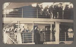 Nurses and soldiers on a troop ship. The women are singing while the soldiers look on; a chaplain appears on the far right, so the scene may be of a service.