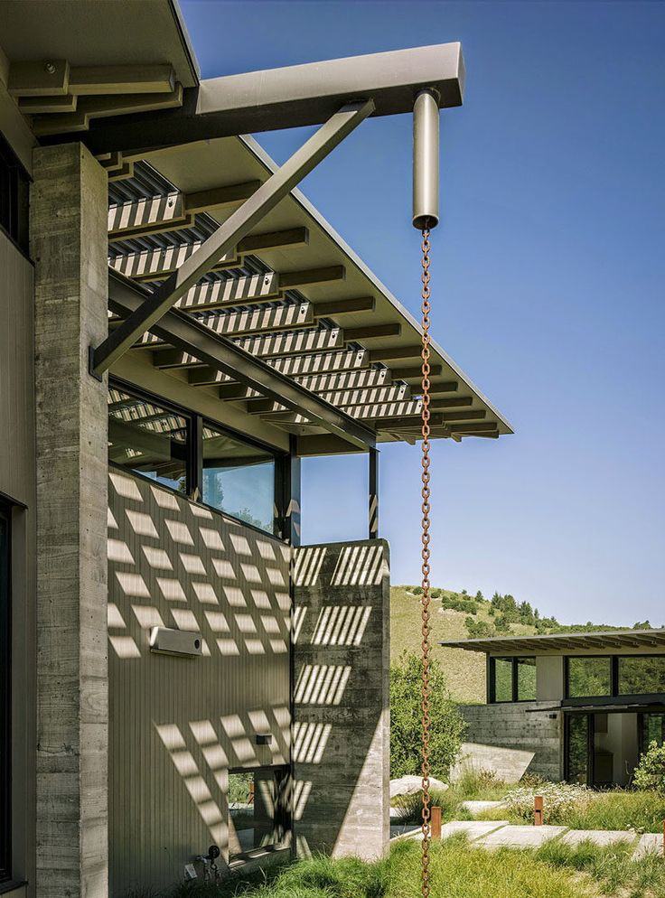 14 Modern Homes That Use Rain Chains To Divert Water // This rain chain has a design reminiscent of an oil pulley, creating an industrial look.