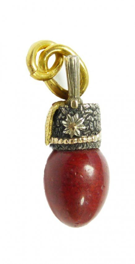 """Faberge Purpurin silver and gold miniature egg pendant. Has ovoid shape topped with figural silver enameled helmet design. Has gold suspension loop. Suspension loop holds workmaster marks of Emiliyarn Kuznetsov and Moscow town marks. Measures 3/4"""" (1.9cm). Total weight of 1.1dwt."""
