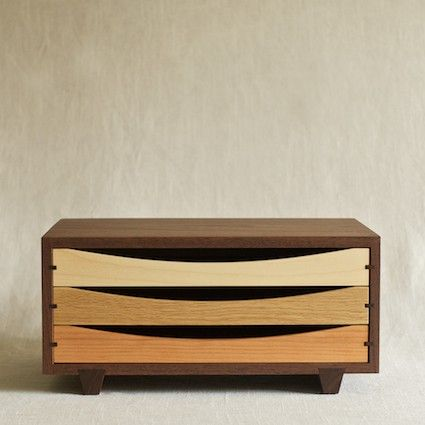 Designed and handcrafted by Isao Aoyanagi of Arms Woodcraft Workshop in Hokkaido. The tricolor desktop chest is handmade from start to finish by one craftsman in the woodworking town of Asahikawa in Hokkaido, Japan. The chest is beautifully and precisely crafted to showcase the gradient of wood tones. The frame, feet and drawer tracks are walnut, and the gliding drawers are maple, oak and cherry.