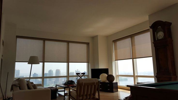 Electric roller shades by NY City Blinds adorn the windows of this New York City living room.