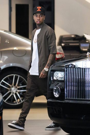 Celebrity Sneakers Style: Tyga at a luxury car dealership wearing Vans laceup sneakers.