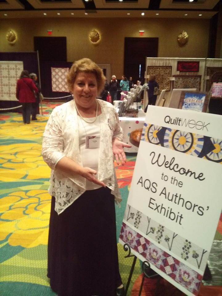 Linda Hahn points the way to the AQS Authors' Exhibit.