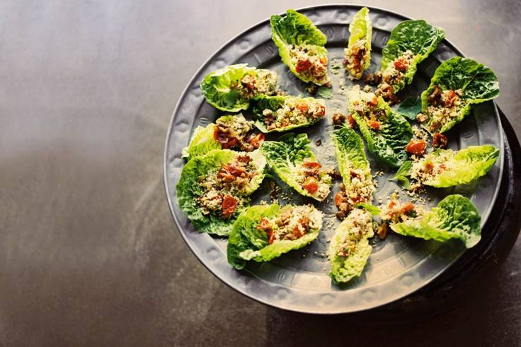 Zin in een chic hapje? Ovengeroosterde groenten met noten en couscous op blaadjes babyromaine.