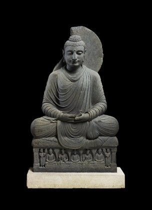 Seated Buddha in dhyāna. The major drapery folds, chiefly in well-rounded ridges and terraces, are flattened at the knees to form low strips. The neckline, in high relief, is somewhat plunging, a semi-circular edge of the robe overlaps the seat while gathered drapery spreads from the left wrist to lie almost flat beside it and another edge is seen below the right forearm;