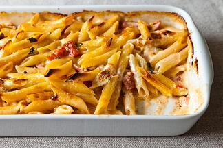 gather your cheeses; mix them into a slurry with canned tomatoes, basil, and a pint of cream in a big bowl. Boil a pound of pasta briefly, then drain and add that in too.