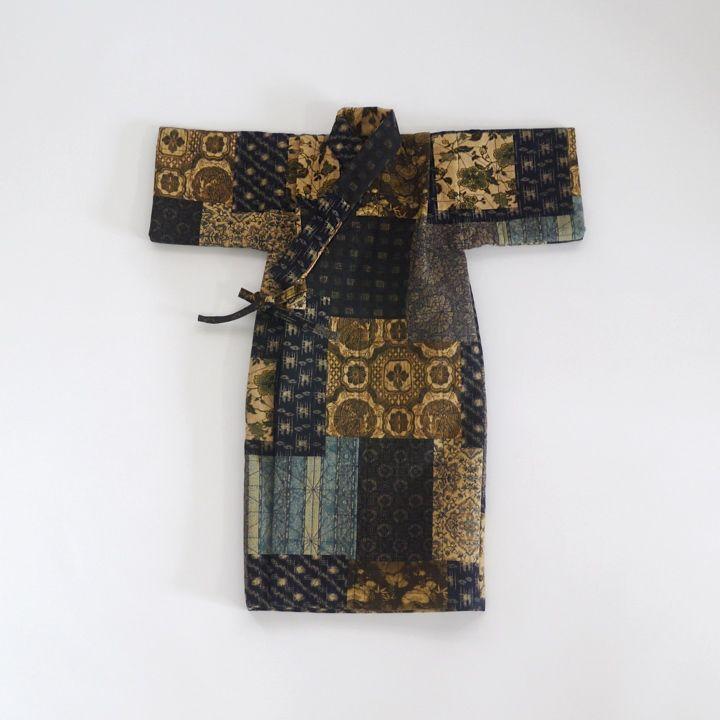 9枚のハギレをつなげたデザインがまるで『寄せ着物』のようなおしゃれな和調木綿を、ミシンで麻の葉模様にキルティングした男の子用のレトロな産着です。