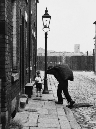 Shirley Baker - Coalman making a delivery. Salford, Manchester, 1964. Notice the manhole cover removed ready for the bag of coal to be tipped into the cellar. Notice also the gas mantle in the street lamp.