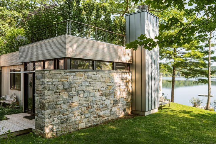 Lush greenery tops one half of this three-bedroom residence on the shore of Connecticut's Lake Wononscopomuc