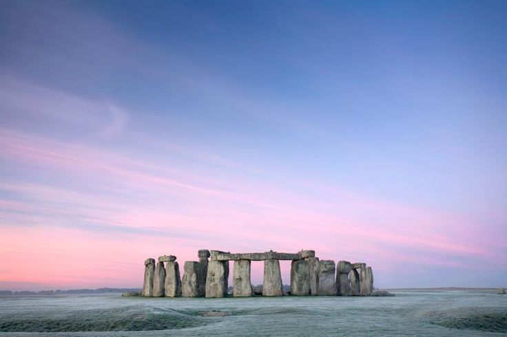 Bands of pink and purple streak the sky over Stonehenge at dawn. PHOTOGRAPH BY PHILIP KRAMER, GETTY IMAGES