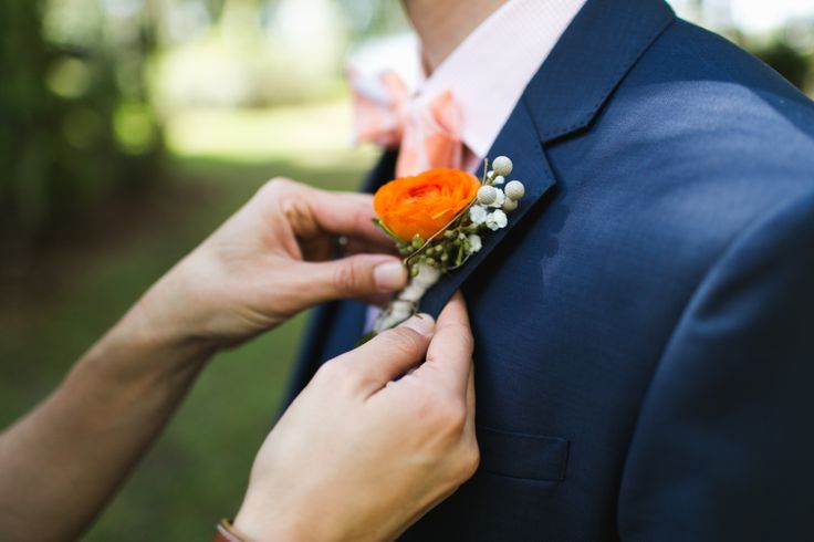 the groom's boutonniere of orange ranunculus, silver brunia, baby's breath is wrapped in satin ribbon and grapevine.
