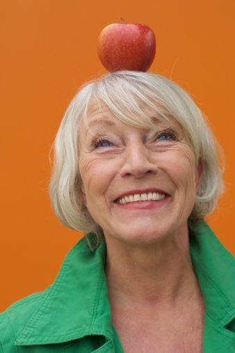 Stock Photo : Senior woman balancing an apple on her head