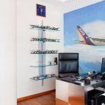 Кабинет заказчика стилизован под интерьер самолета: дизайнерская мебель, рулонные шторы, фреска с парящим в облаках самолетом, скругленные формы потолков со светодиодной подсветкой. На стенах нанесена декоративная штукатурка с легким глянцем.