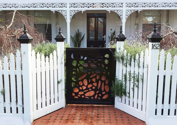 A decorative screen used on a gate modernizes the entry to a Victorian cottage. This is our 'Cayman' design cut in mild steel. ~QAQ