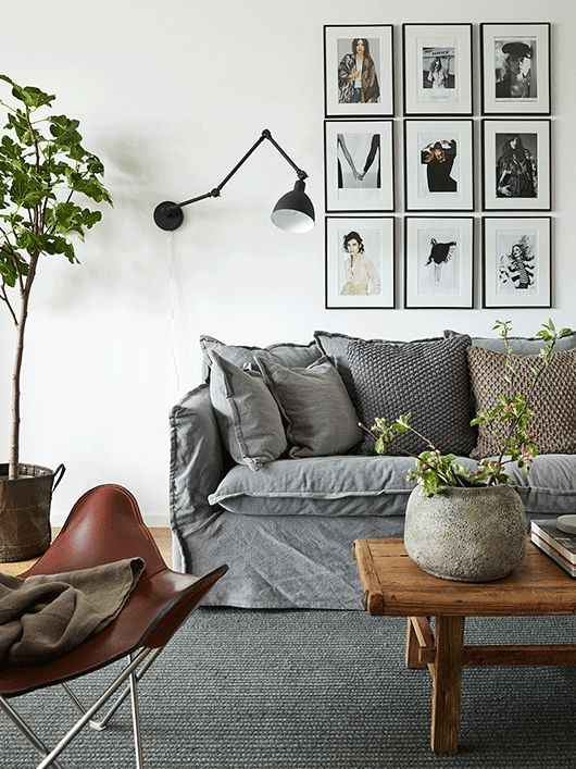 There is so much I like about this photo.  The gray on gray sofa and rug.  The mix of wood and wool and linen.  The wall mounted lighting and the gallery wall.  LOVE IT!
