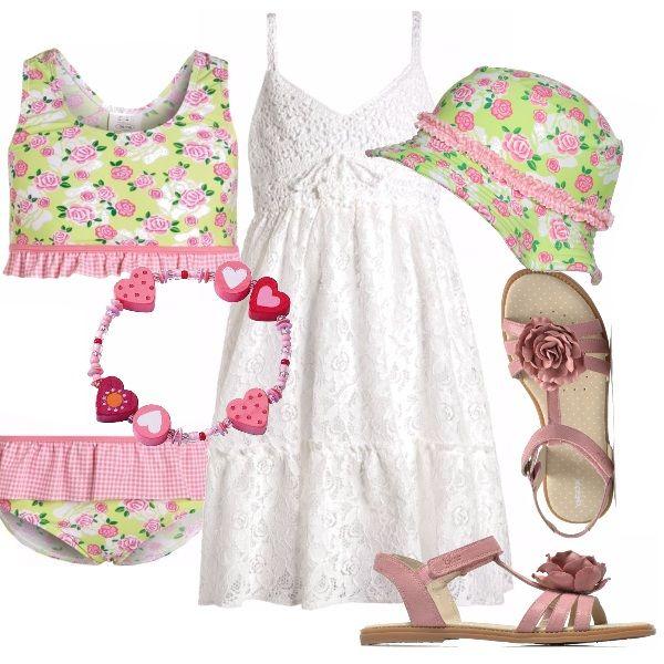 Abitino bianco in fresco cotone, con corpino lavorato all'uncinetto. Bikini verde acido con fantasia di roselline, così come il cappellino coordinato. Sandaletto in pelle rosa, con fiore applicato, grazioso braccialetto in legno.