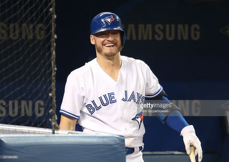Josh Donaldson #20 of the Toronto Blue Jays laughs as he gets ready to bat from…