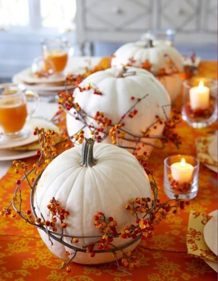 White pumpkins encircled by bittersweet vine and set along an orange table runner create a striking table arrangement