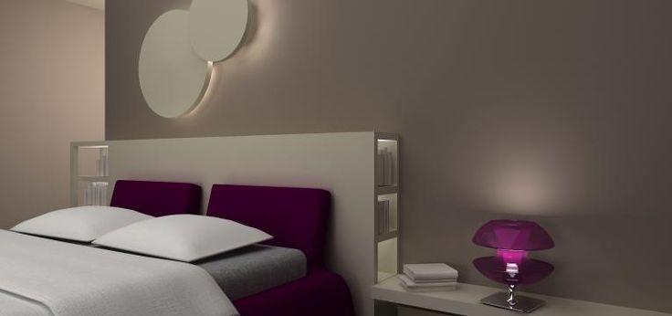 Il progetto prevede una sorta di parate attrezzata in cartongesso che unisce la funzione di testiera del letto a quella di contenitore e di comodino. L'effetto è quello di una composizione omogenea e ben strutturata che unisce la forma alla funzionalità degli elementi. A completare la parete del letto c'è una composizione sempre in cartongesso che nasconde una luce d'atmosfera. Nasce così una lampada a parete che arreda e caratterizza la camera. Anche l'armadio è incassato nel cartongesso…