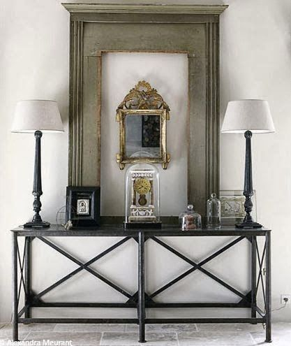 mirror within a larger frame above console table flanked by two lamps