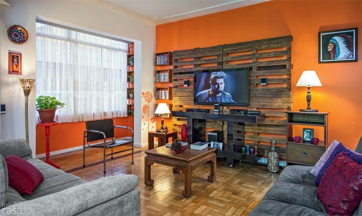 Inspirada na capa de uma edição de MINHA CASA, Eliane Felipeto criou esta sala para seu apê. Além dos paletes no painel da TV, o ambiente tem espaço para plantas e adesivos decorativos. A tinta alaranjada da parede é a acrílico semibrilho General, ref. P125, da Suvinil.