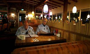 Steve Rubin a World War II veteran and Henry Miller, a Vietnam War pilot, members of The Retired Senior Volunteer Patrol grab a late meal at a restaurant while out on patrol in San Diego, California. The retirees perform minor duties which frees up regular serving officers' time